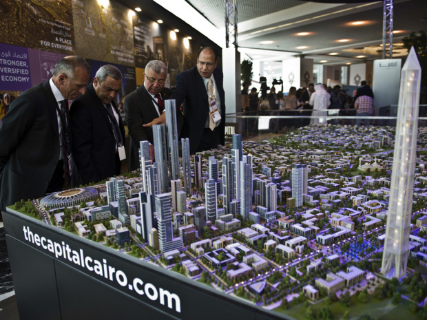 "A delegation looks at a scale model of the new Egyptian capital displayed at the congress hall in the Red Sea resort of Sharm el-Sheikh on March 14, 2015. Egypt plans to build a new administrative and business capital east of Cairo that will house five million people and feature a theme park ""four times bigger than Disneyland"", a minister announced at a global investor conference. AFP PHOTO / KHALED DESOUKI        (Photo credit should read KHALED DESOUKI/AFP/Getty Images)"